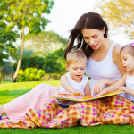Photo of young brunette woman teaching two sweet kids, cheerful